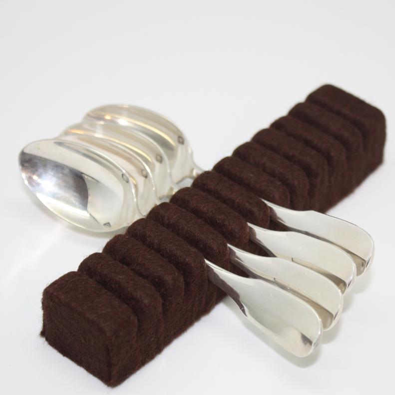 Rangement argenterie: Support de couverts Marron pour 12 cuillères à café/thé ou 12 fourchettes à gâteau. Support pour 12 cuillères à café/thé/moka ou fourchettes à gâteau en argent ou métal argenté. Support en bois, recouvert de tissu anti-oxydant marron. Le ruban adhésif placé en dessous du support permet de fixer ce dernier sur le tissu adhésif collé au fond du tiroir. Module de rangement couverts vendu exclusivement sur le site www.chemindetable.fr. Les chevalets sont des supports en bois, fabriqués avec le plus grand soin etrecouverts de tissu feutré antioxydant, dont la forme en